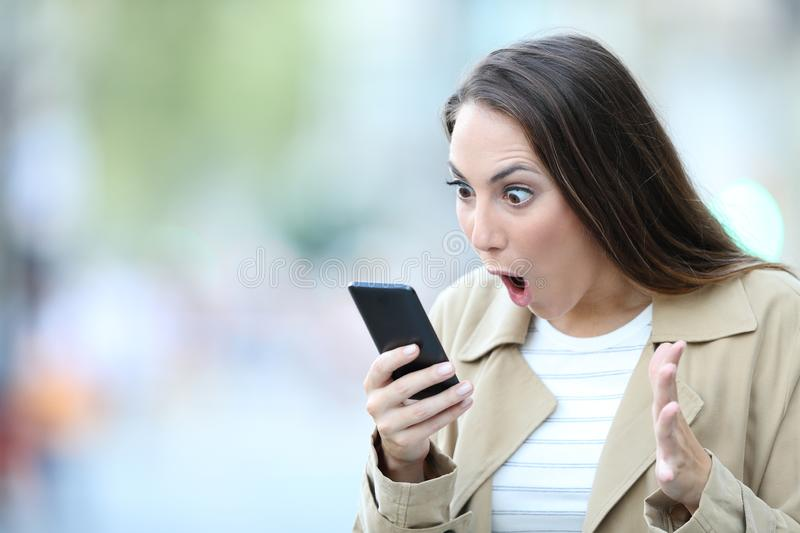 Shocked woman finding surprising news on phone stock images