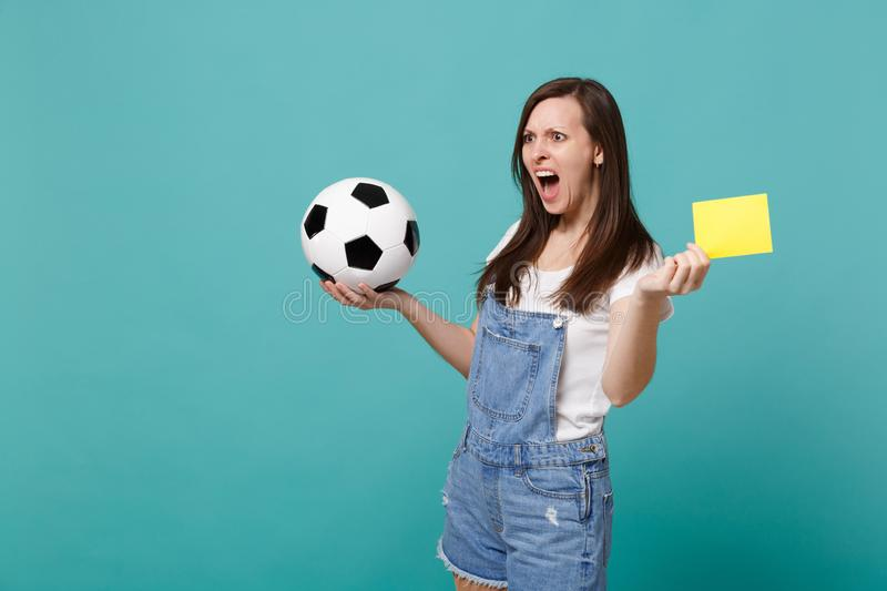 Shocked woman football fan support team with soccer ball, yellow card, propose player retire from field, swearing. Isolated on blue turquoise background. People stock photo