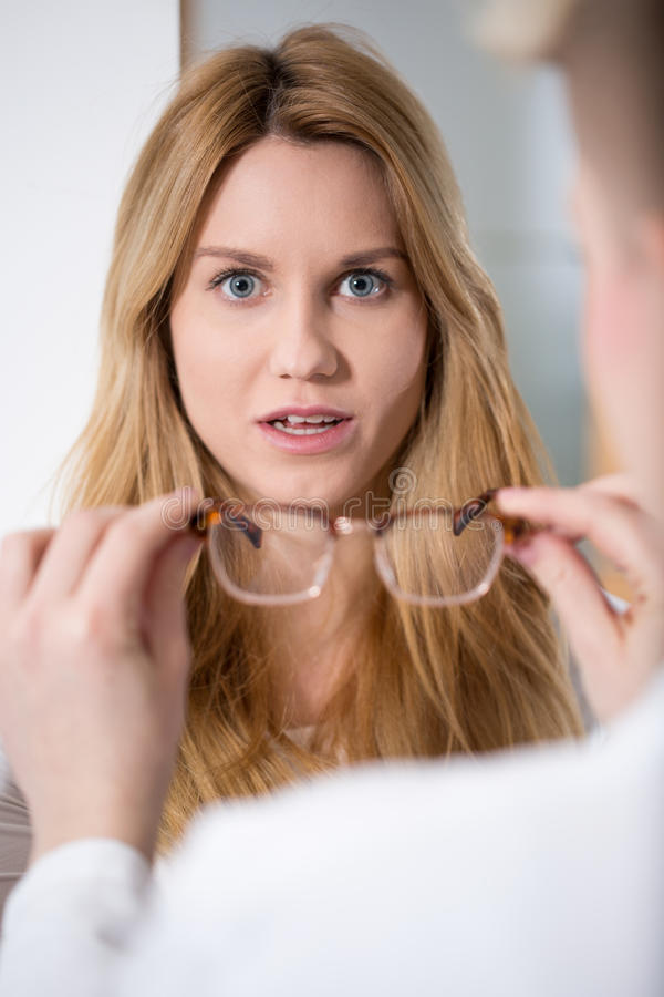 Shocked woman going to wear glasses. Beauty shocked women going to wear glasses stock images