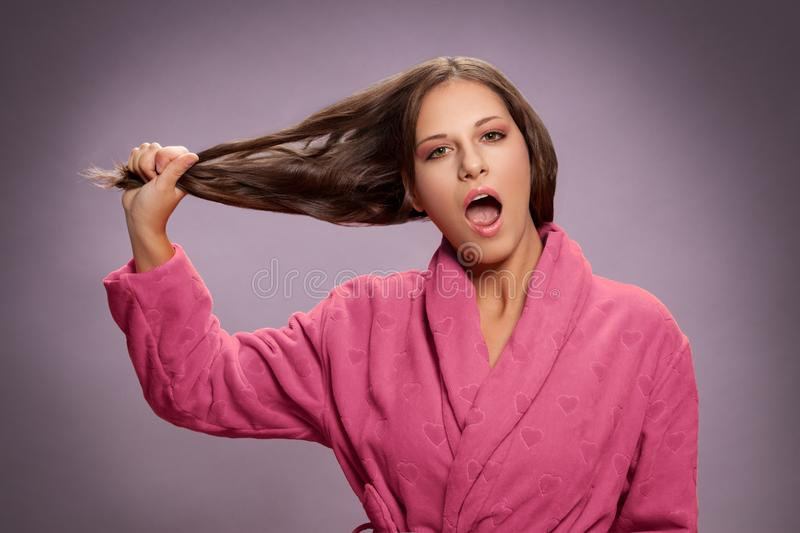 Shocked woman holding her dry damaged hair stock photography