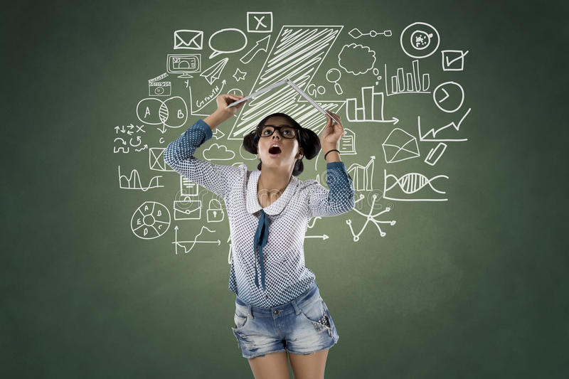 Shocked woman holding laptop over her head. In front of icons on chalkboard stock images