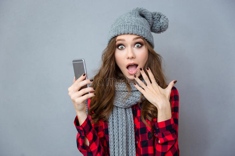 Shocked woman holding smartphone. Portrait of a shocked woman holding smartphone over gray background royalty free stock photos