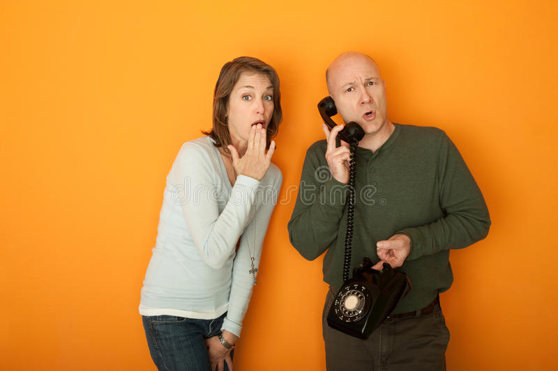 Shocked Woman Listening To Telephone Conversation. Shocked Caucasian woman with hand on mouth listening to a telephone conversation royalty free stock photography