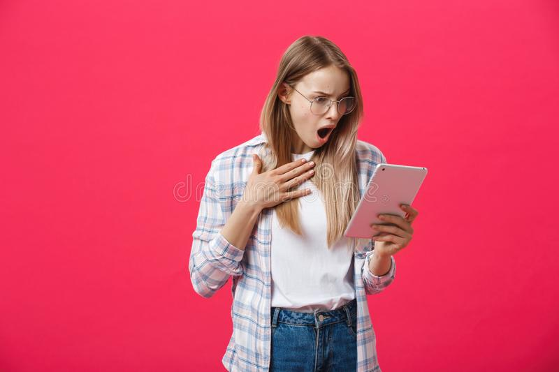 Shocked woman looking at digital tablet with surprise and shock over pink background. Astonishment or hot news in royalty free stock images