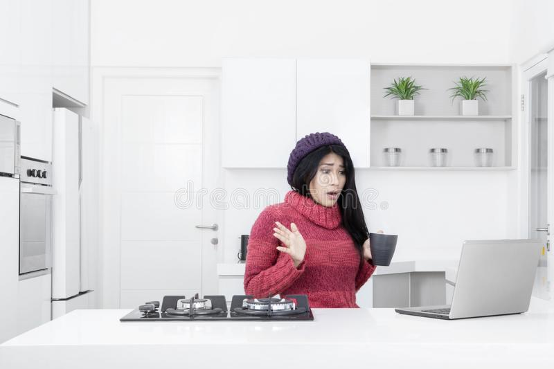 Shocked woman looking at laptop in the kitchen stock photo