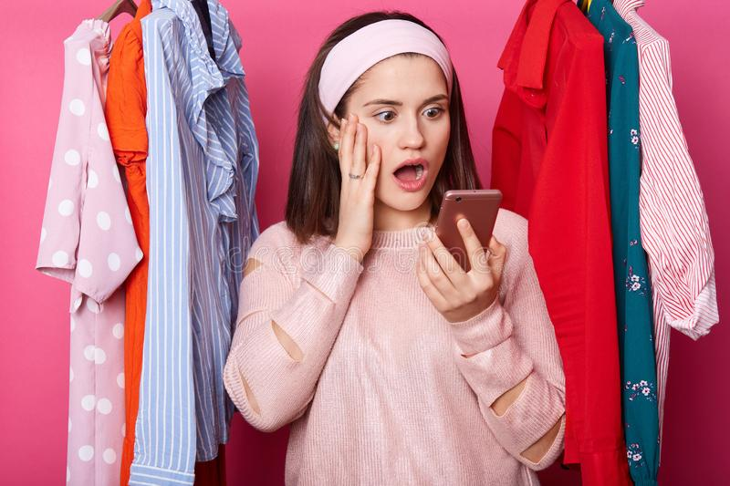 Shocked woman looks at smartphone display, wath ballance of credit card via app, dark haired lady keeps palm on cheek and looks. Surprisingly at her gadget royalty free stock image