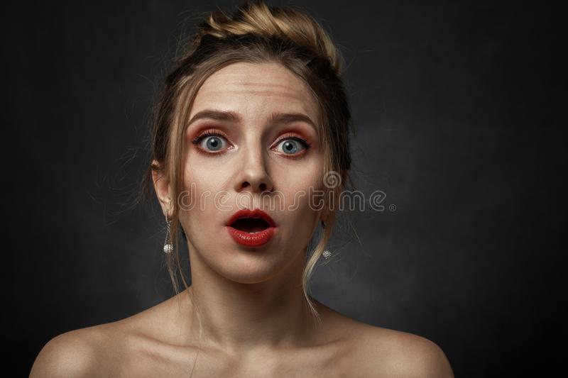 Woman open mouth. Shocked woman with open mouth on black background looking at camera royalty free stock images