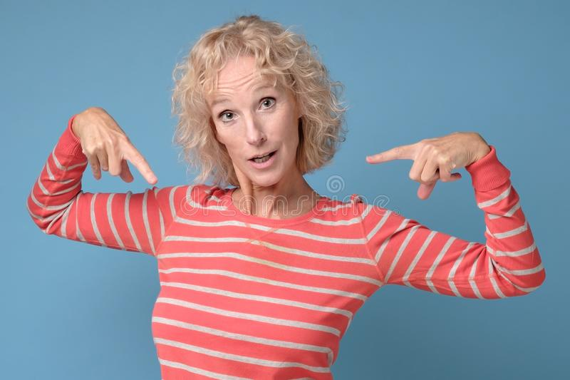 Shocked woman point at herself holding finger on chest surprised being accused. stock photo