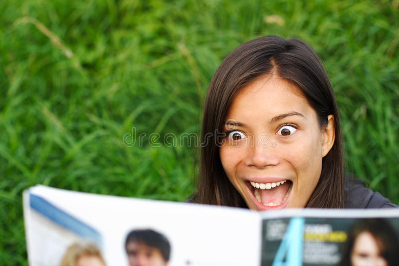 Shocked woman reading magazine royalty free stock photography