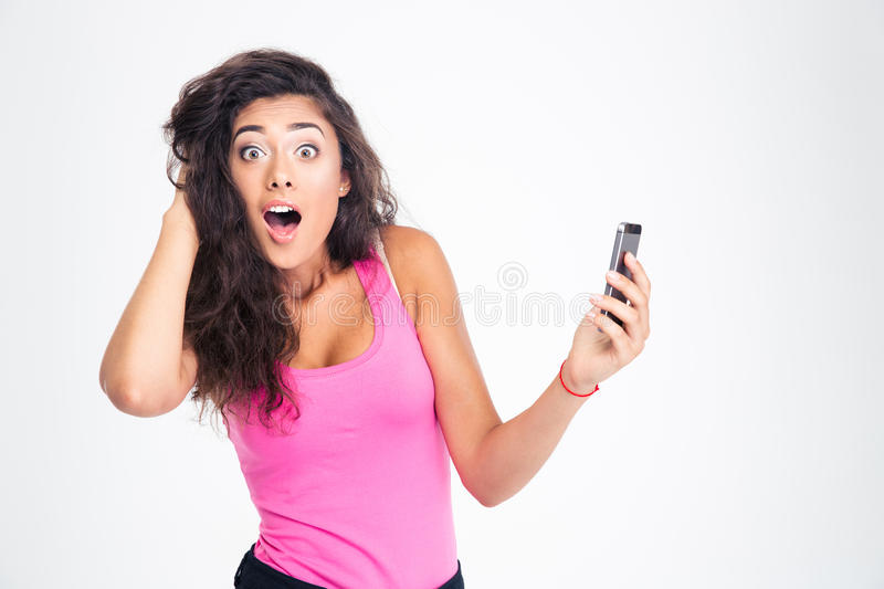 Shocked woman standing with smartphone. Shocked young woman standing with smartphone and looking at camera isolated on a white background stock image