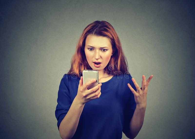 Shocked woman watching news on smartphone royalty free stock photo