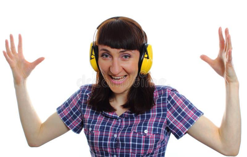 Shocked woman wearing protective headphones stock photo