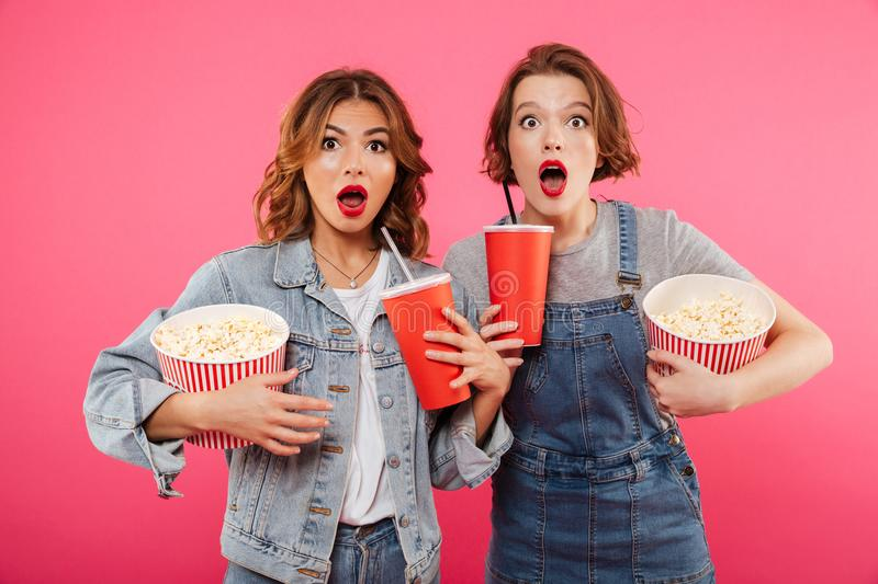 Shocked women friends eating popcorn watch film. Photo of two shocked women friends standing isolated over pink background. Looking camera eating popcorn watch royalty free stock images