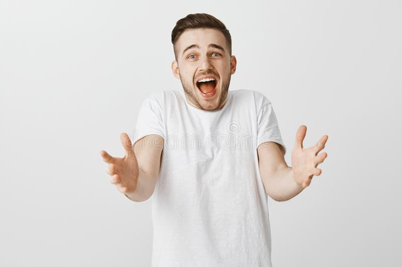 Shocked worried and sad guy with beard pulling hands towards camera shrugging and shouting from regret being upset. Favorite team lost match standing displeased royalty free stock images