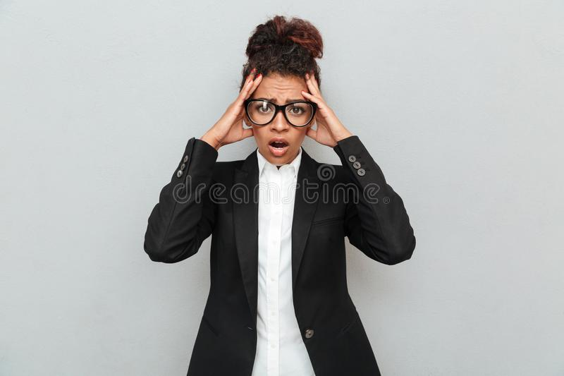 Shocked young african business woman. Image of shocked young african business woman standing over grey wall looking camera royalty free stock photo