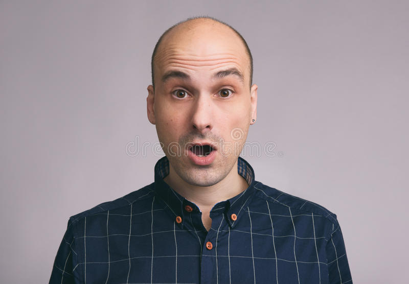 Shocked young bald man with open mouth royalty free stock photography