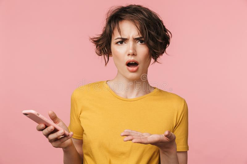 Shocked young beautiful woman posing isolated over pink wall background using mobile phone stock photography