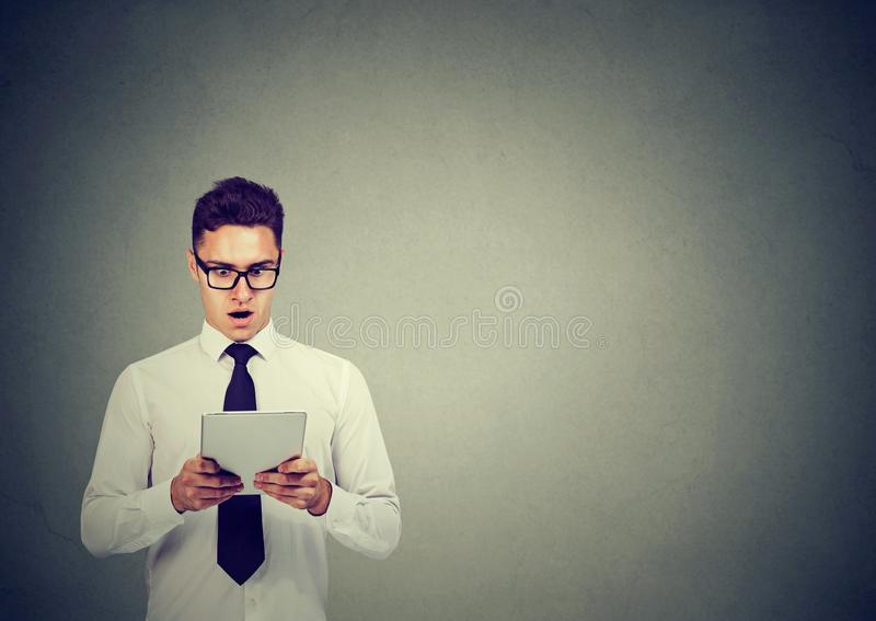 Shocked young business man in glasses using a tablet stock photography