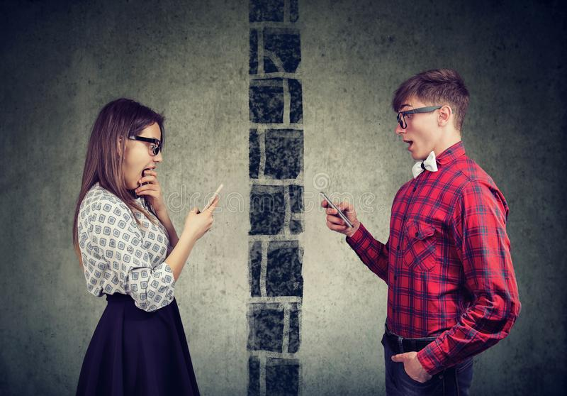Shocked couple man and woman separated by wall texting each other on mobile phone. Shocked young couple men and women separated by wall texting each other on stock image