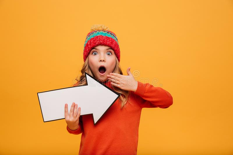 Shocked Young girl in hat pointing with paper arrow away. Shocked Young girl in sweater and hat pointing with paper arrow away and looking at the camera over stock photos
