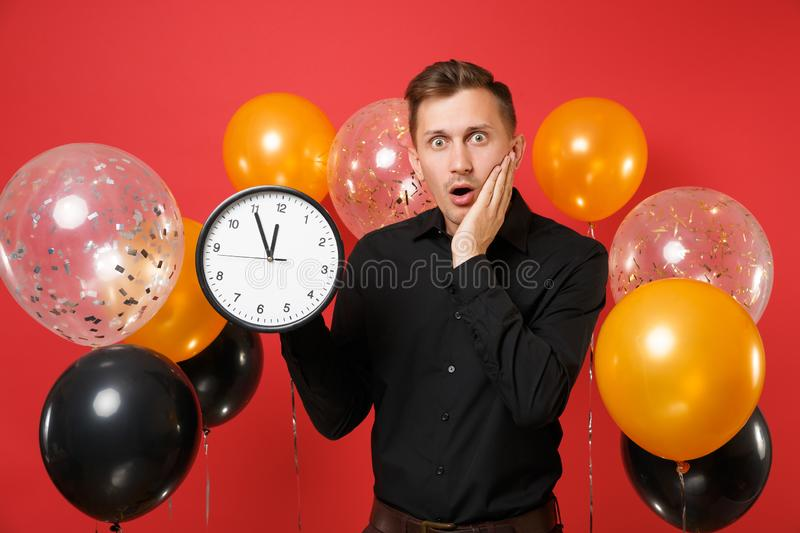 Shocked young man in black classic shirt keeping hand on face holding round clock on red background air balloons. Time stock photography