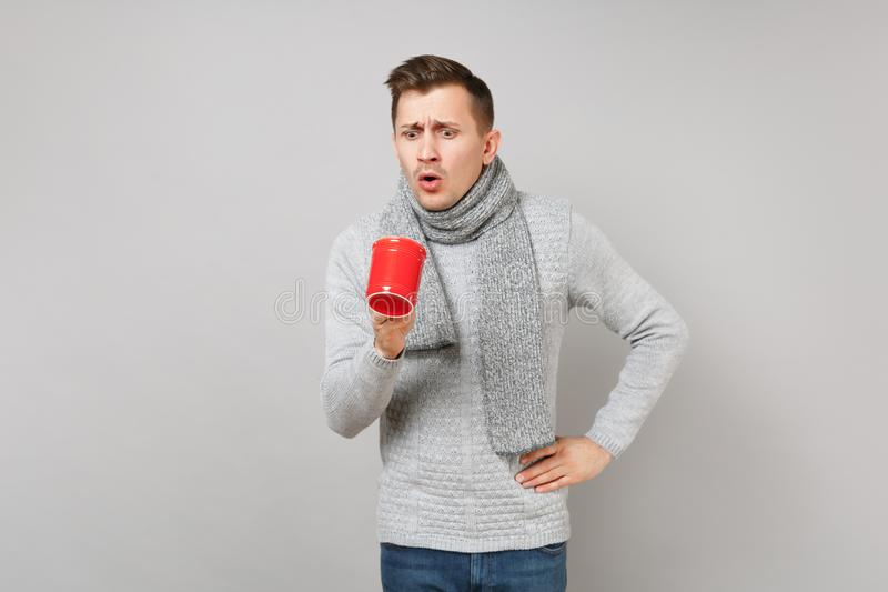 Shocked young man in gray sweater, scarf looking into red cup of coffee or tea on grey wall background. Healthy royalty free stock image