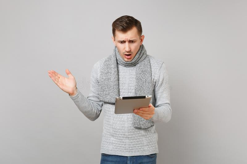 Shocked young man in gray sweater, scarf using tablet pc computer, spreading hands isolated on grey background. Healthy royalty free stock image