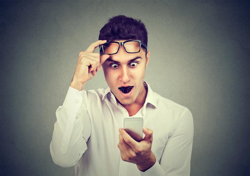 Shocked young man looking reading news on smart phone stock photography