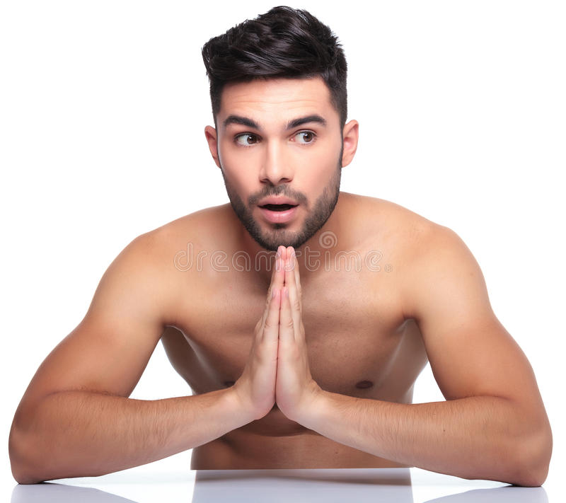 Shocked young man is praying. Shocked young man is looking away to his side while praying on white background stock photo