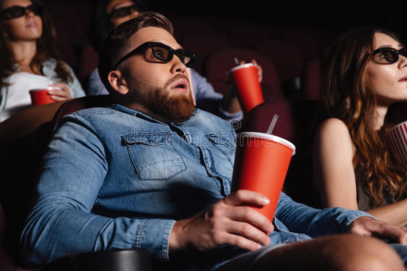 Shocked young man sitting in cinema watch film stock photography