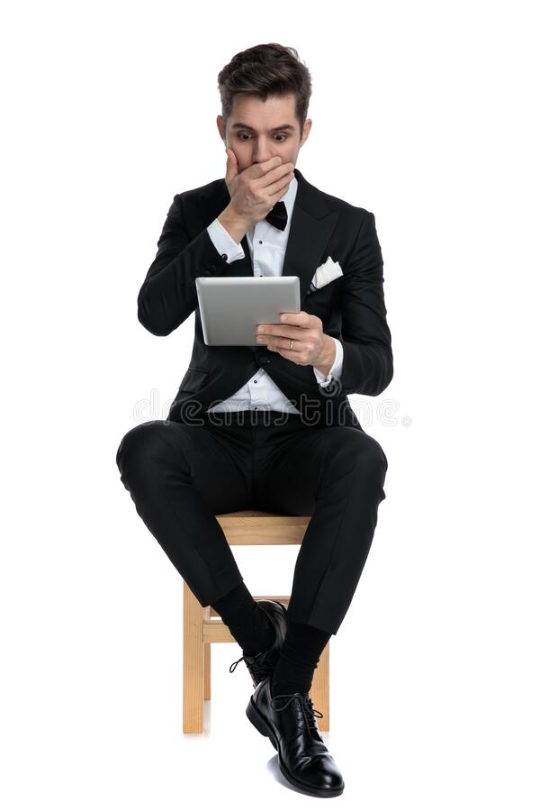 Shocked young man covering mouth and holding tab stock images