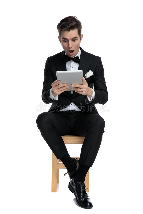 Shocked young modern man holding tab stock photo