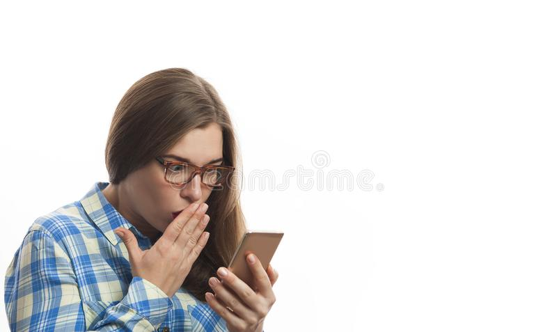 Shocked young woman in blue plaid shirt holding smartphone in hands. Atractive female standing and posing over white background royalty free stock images