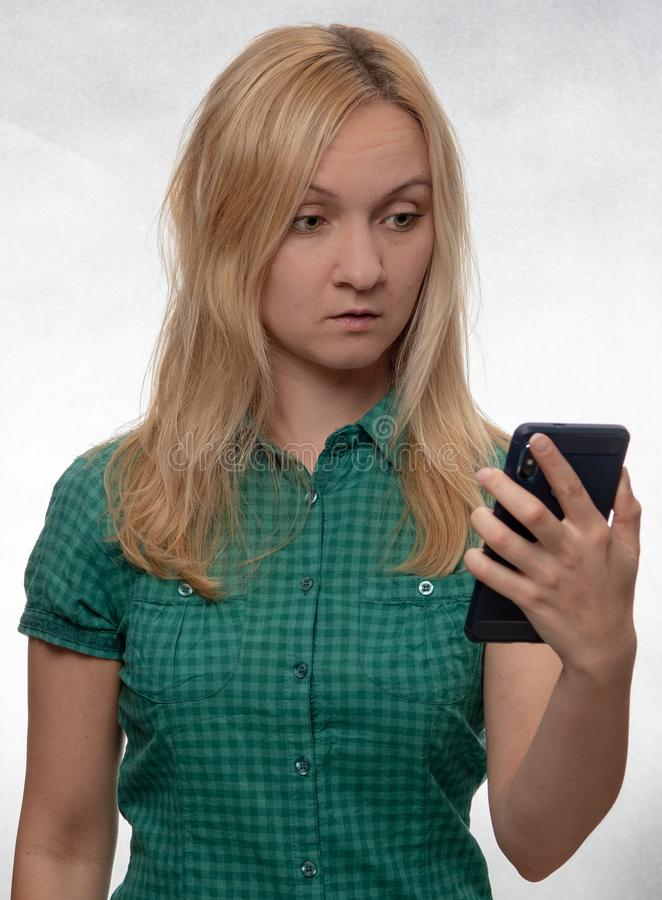 Shocked young woman in casual green shirt with smartphone in hand looking at phone royalty free stock photography