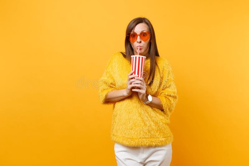 Shocked young woman in fur sweater and heart orange glasses drinking cola or soda from plastic cup isolated on bright. Yellow background. People sincere royalty free stock image