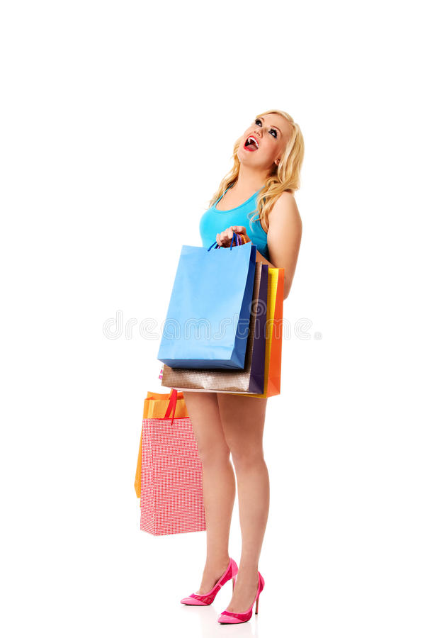 Shocked young woman holding shopping bags stock photos