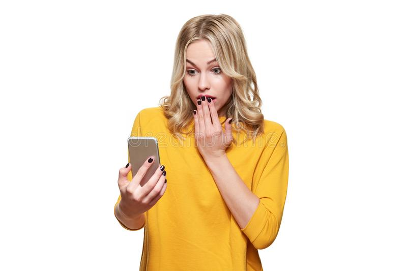 Shocked young woman holding up her mobile phone, reading shocking news. Woman in disbelief, isolated over white background. royalty free stock photography
