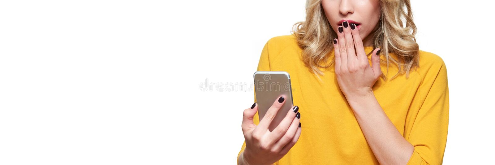 Shocked young woman holding up her mobile phone, reading shocking news. Woman in disbelief, isolated over white. Shocked young woman holding up her mobile phone stock photo