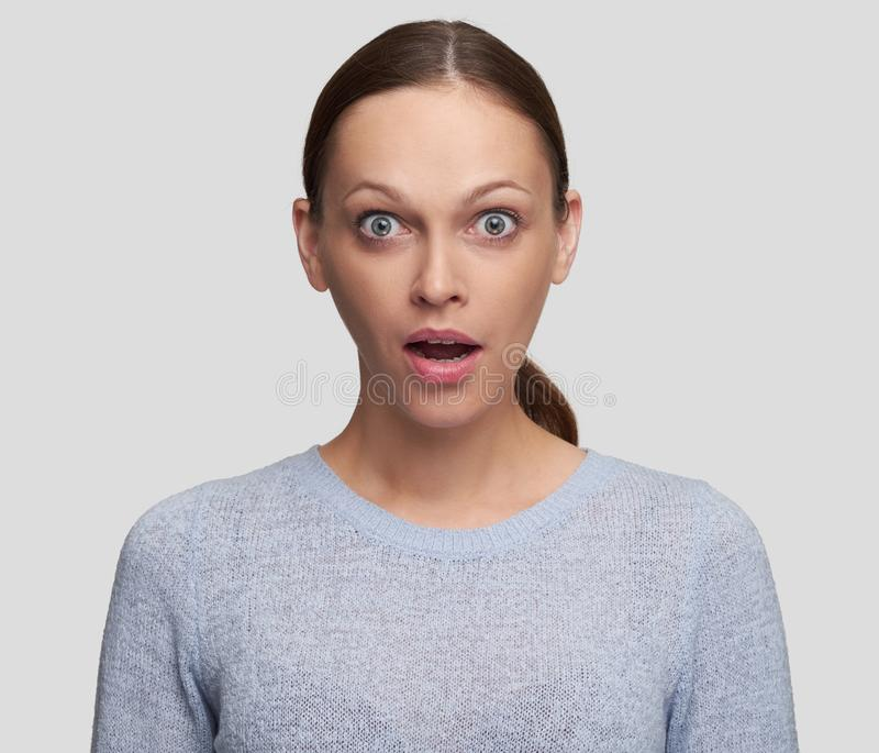 Shocked young woman looking at camera stock image