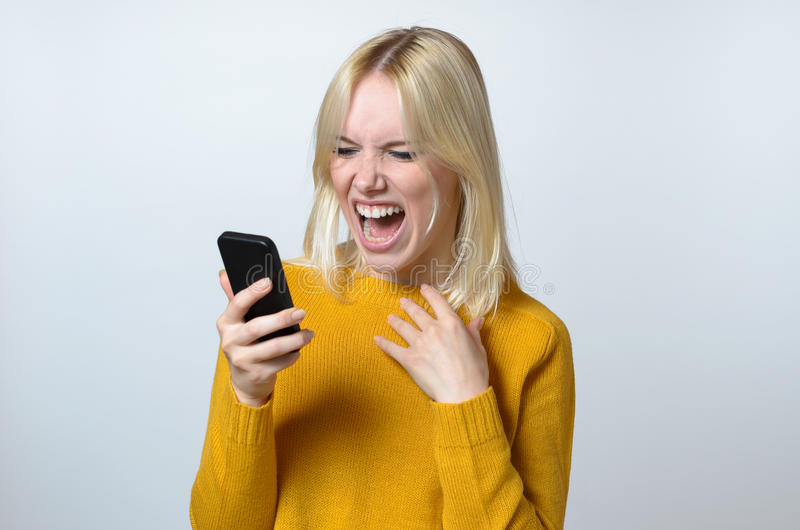 Shocked Young Woman Looking at her Mobile Phone. Blond Young Woman Showing Shocked Expression While Looking at her Mobile Phone Against White Background royalty free stock photo