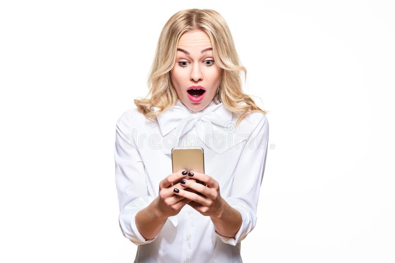Shocked young woman looking at her mobile phone, screaming in disbelief. Woman staring at shocking text message on her phone. Shocked young woman looking at her royalty free stock image