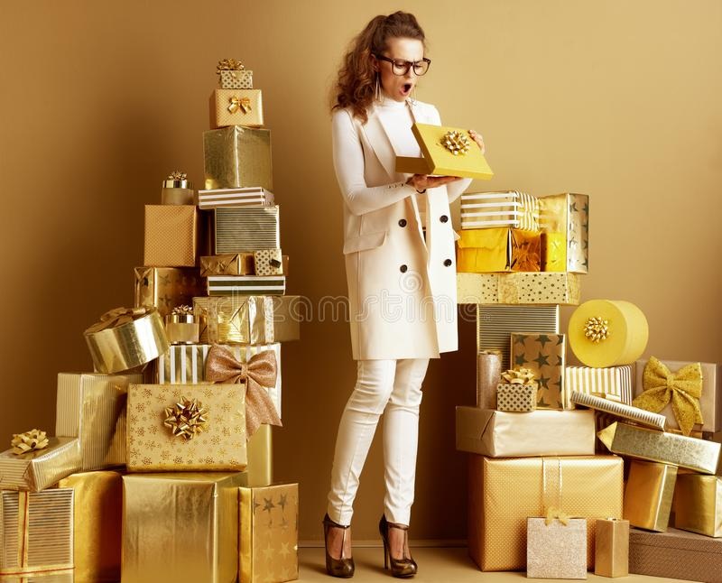 Shocked young woman opening golden present box with bow royalty free stock photography