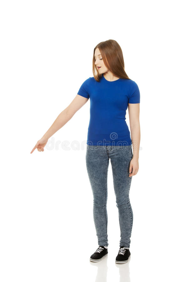 Shocked young woman pointing down. royalty free stock photo