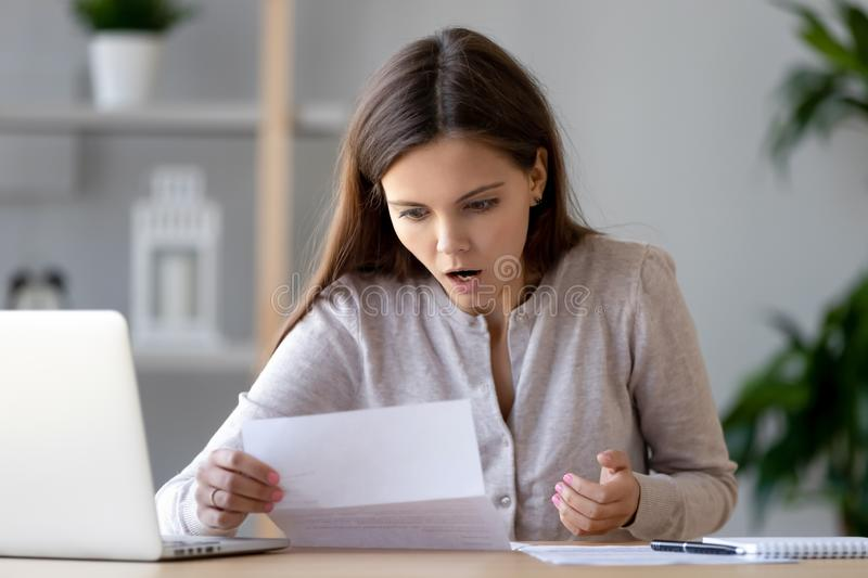 Shocked young woman reading unexpected bad news, sitting at desk. Shocked young woman reading unexpected bad news, financial problem, bills or debt, sitting at stock photo