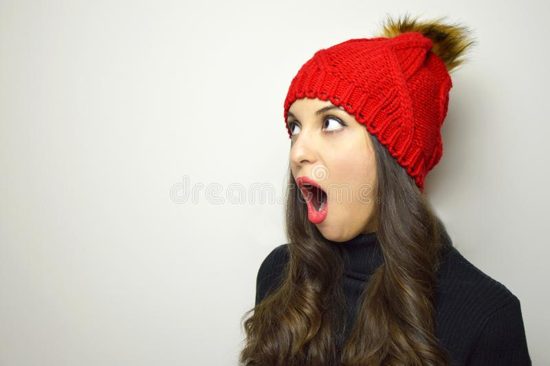 Shocked young woman with red hat looking to the side your product on gray background. Copy space. royalty free stock photography