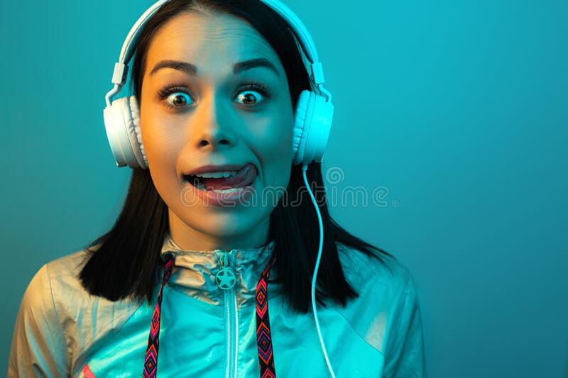 Shocked young woman in 90s style sport outfit with white headphones listening to music in neon lights at studio. Shocked young woman in 90s style sport outfit royalty free stock photos