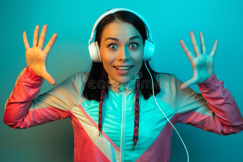 Shocked young woman in 90s style sport outfit with white headphones listening to music in neon lights at studio. Shocked young woman in 90s style sport outfit royalty free stock images