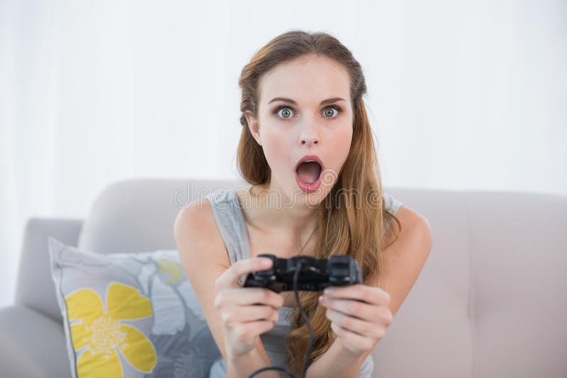 Shocked young woman sitting on sofa playing video games stock photo