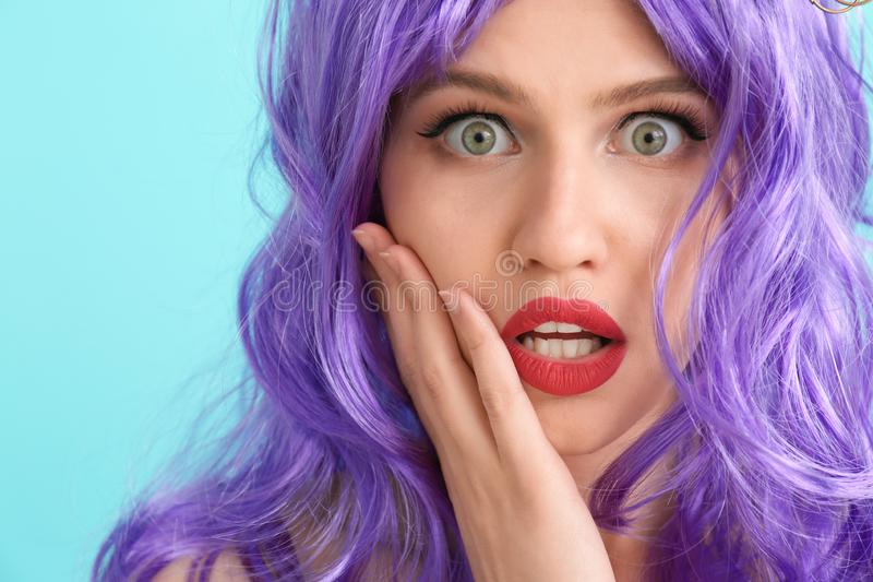 Shocked young woman with unusual hair on color background stock photo