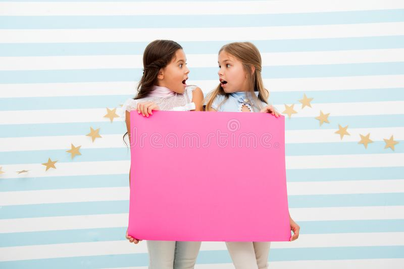 Shocking announcement concept. Amazing surprising news. Girl hold advertising banner. Girls kids holding paper banner royalty free stock images